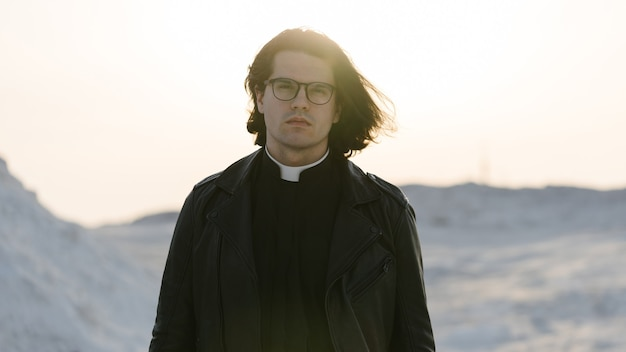 Beau portrait de jeune prêtre à l'extérieur au coucher du soleil.