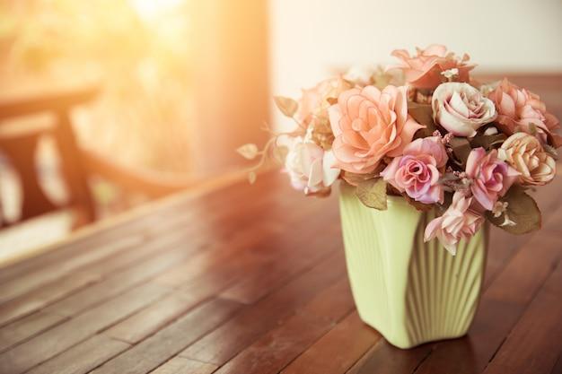 Beau pot de fleur rose sur la décoration de la maison de table en bois nature avec la lumière du soleil ton couleur vintage.