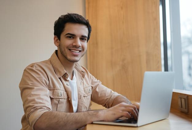 Beau programmeur indien à l'aide d'un ordinateur portable travaillant à domicile