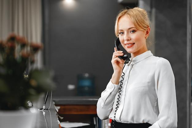 Beau réceptionniste de l'hôtel femme sympathique parler au téléphone se bouchent