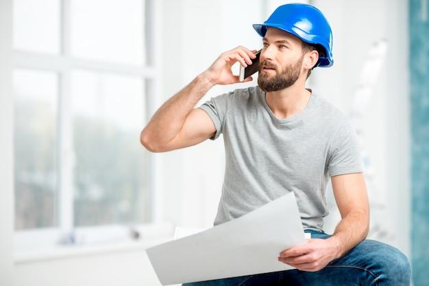 Beau réparateur ou constructeur en casque parlant avec un téléphone avec des dessins à l'intérieur blanc