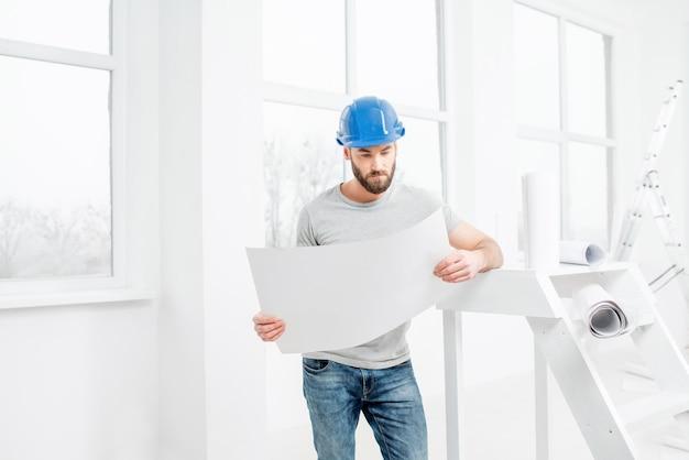 Beau réparateur ou constructeur en casque travaillant avec des dessins sur la rénovation de l'intérieur de l'appartement