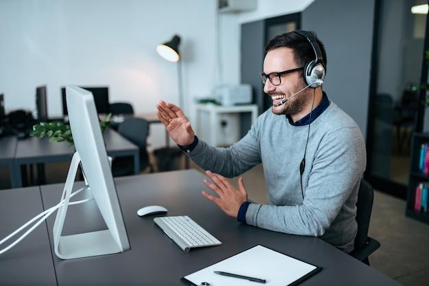 Beau représentant du service d'assistance parlant au client dans le centre d'appels