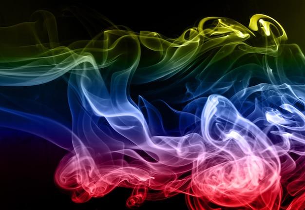Beau résumé de fumée colorée sur fond noir, mouvement de feu