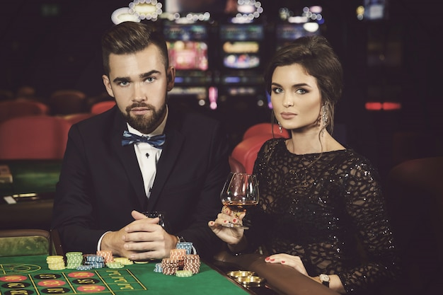 Beau et riche couple jouant à la roulette au casino