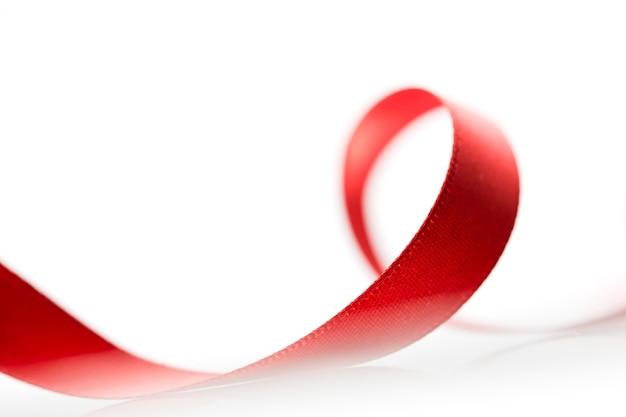 Beau ruban rouge en tissu sur une surface blanche