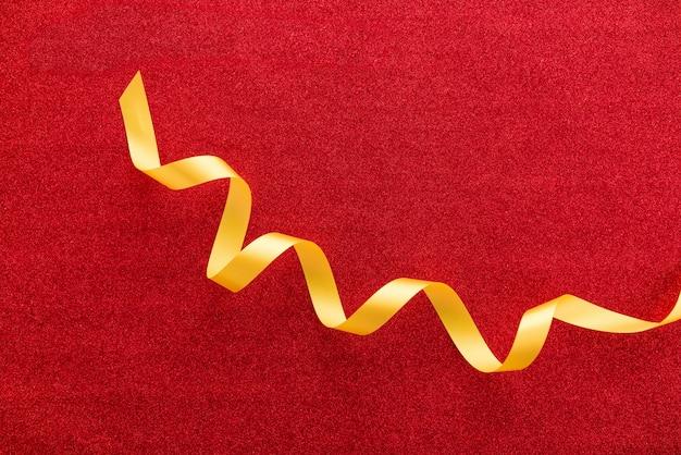 Beau ruban de satin brillant bouclé doré sur fond de papier cadeau ou cadeau de paillettes rouge coloré