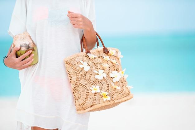 Beau sac avec fleurs de frangipanier et noix de coco dans des mains féminines