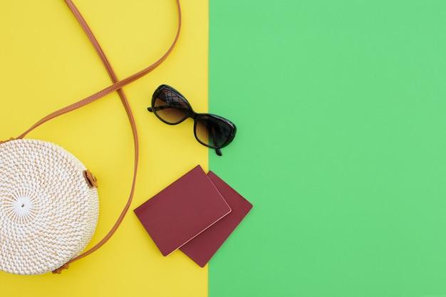 Beau sac à main rond en paille et lunettes de soleil avec passeports sur fond jaune-vert. sac à main tendance.