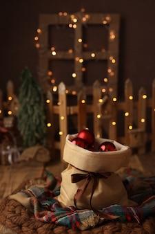 Beau sac de noël avec des cadeaux faits de boules rouges d'arbre de noël sur un fond foncé
