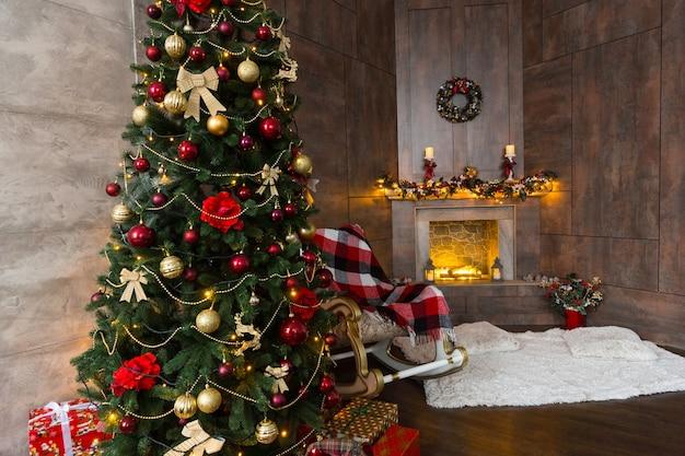 Beau salon avec chaise berçante avec une couverture, cheminée enflammée moderne décorée et grand sapin de noël avec beaucoup de cadeaux et décorations différentes