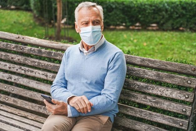Beau senior adulte avec masque facial dans un parc pendant la pandémie de virus corona
