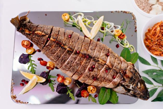Beau service cuit au four entier et coupé en morceaux de poisson.