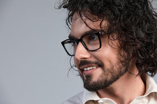 Beau, souriant, jeune homme aux cheveux longs foncés et lunettes élégantes isolés sur fond gris, dans des vêtements élégants, positifs et réussis dans la carrière et les affaires.
