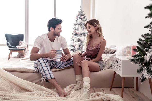 Beau sourire. beau jeune homme barbu avec une tasse dans son sourire à sa femme alors qu'il était assis sur le lit
