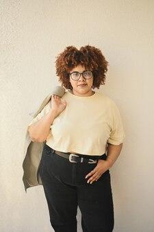Beau sourire heureux sinueuse taille plus femme noire africaine cheveux afro posant un jean tshirt beige