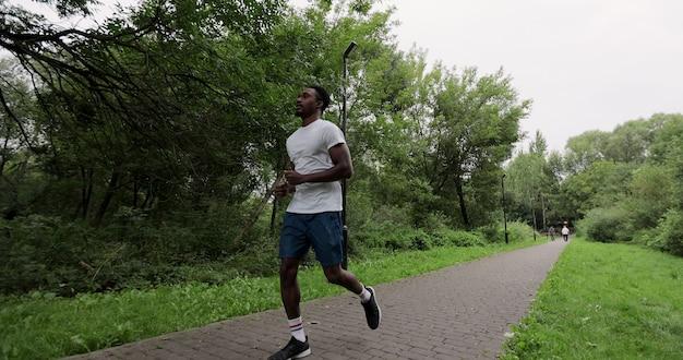 Beau sportif afro-américain exerçant à l'extérieur au ralenti. un homme en tenue de sport court parmi les arbres du parc. concept de mode de vie sain.
