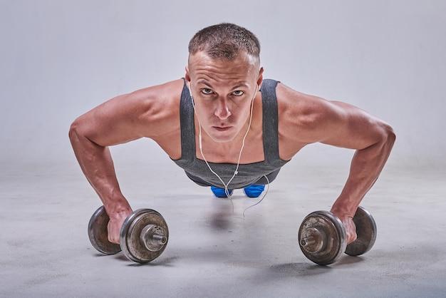 Un beau sportif est pressé du sol avec des haltères dans les mains