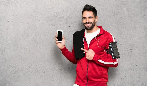 Beau sportif heureux et pointant le mobile sur un mur texturé