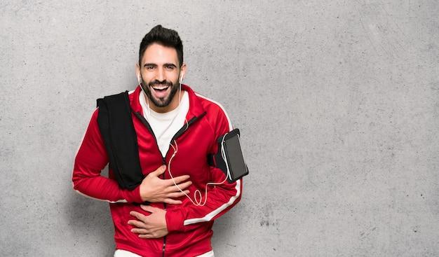 Beau sportif souriant beaucoup en mettant les mains sur la poitrine sur le mur texturé