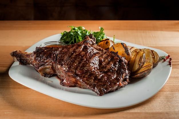 Un beau steak juteux avec salade sur plaque est sur la table en bois.