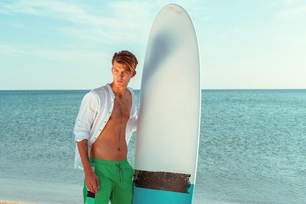 Beau surfeur tenant sa planche de surf