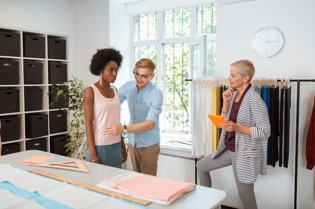 Beau tailleur joyeux mesurant une jeune femme sérieuse regardant un créateur de mode féminin souriant