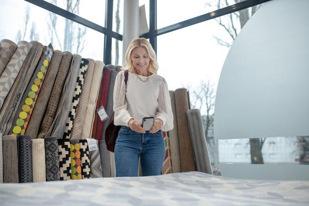 Beau tapis. joyeuse femme debout photographiant un beau tapis, qui est vendu dans un magasin de meubles.