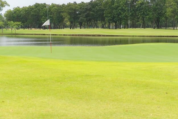 Beau terrain de golf et jardin, étang ou marais sur un drapeau blanc sur un trou en un.