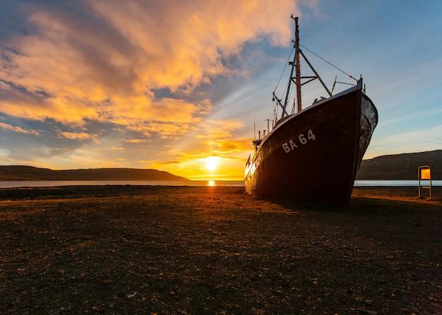 Un beau tir d'un bateau de pêche s'approchant de la plage au lever du soleil