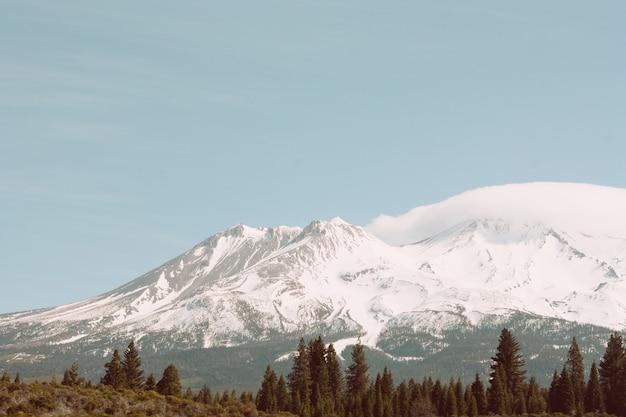 Beau tir d'une haute montagne enneigée avec un ciel bleu clair incroyable