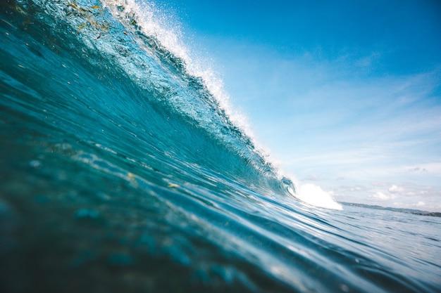 Beau tir d'une vague prenant forme sous le ciel bleu clair capturé à lombok, indonésie