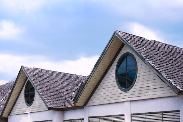 Beau toit de maison en bois avec une fenêtre ronde sur fond de ciel bleu