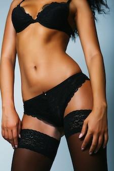 Beau torse bronzé de femme athlétique en lingerie noire et bas