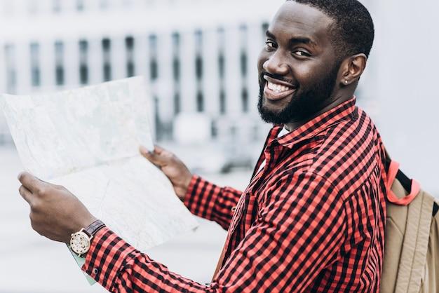 Beau touriste afro-américain heureux avec carte dans la ville moderne