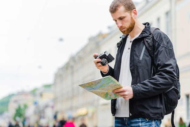 Beau touriste avec appareil photo et carte