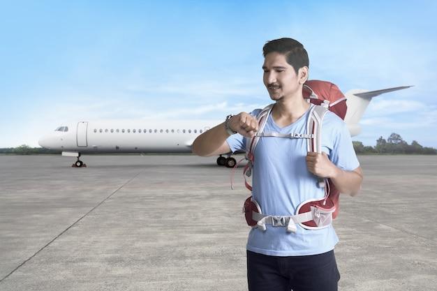 Beau touriste asiatique avec sac à dos vérifiant l'heure avant le départ