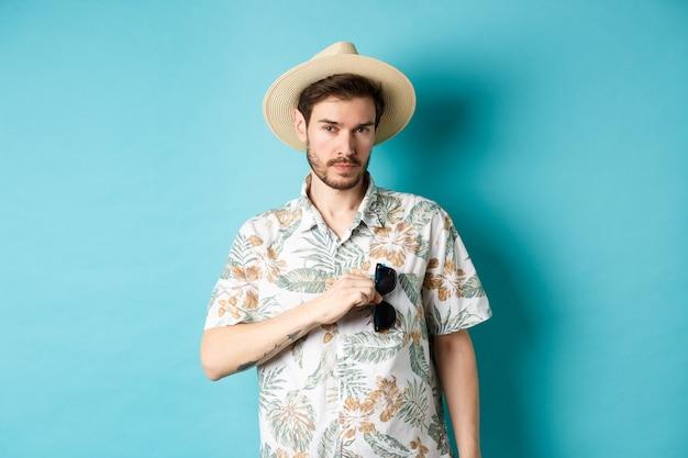 Beau touriste en chemise hawaïenne et chapeau d'été, mettre des lunettes de soleil dans la poche, partir en vacances, debout sur fond bleu.