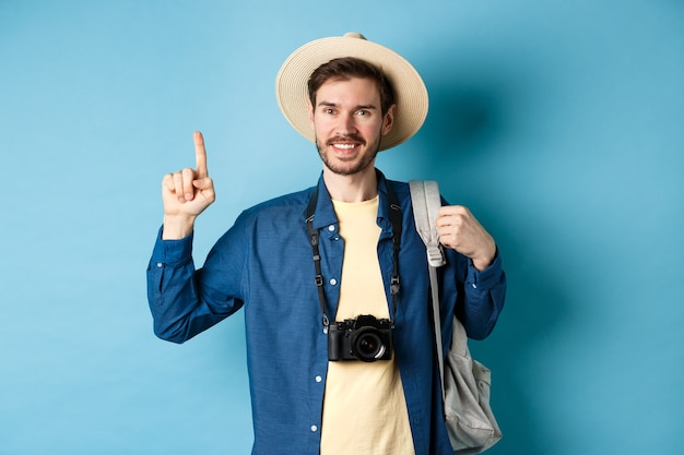 Beau touriste heureux en chapeau d'été, tenant un sac à dos et un appareil photo, pointant le doigt vers le haut sur le logo, recommandant une agence de voyage ou un lieu de vacances, fond bleu.