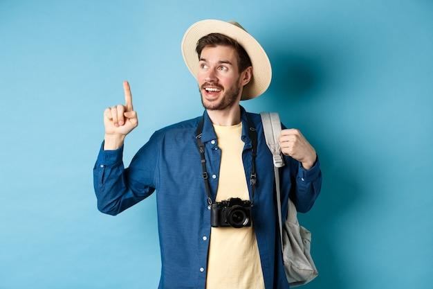Beau touriste à la recherche et pointant vers le haut, voyageant en vacances d'été avec sac à dos et appareil photo, debout sur fond bleu.