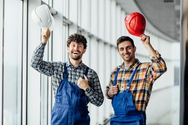 Beau travailleur de la construction partageant l'expérience avec un collègue, tenant un casque