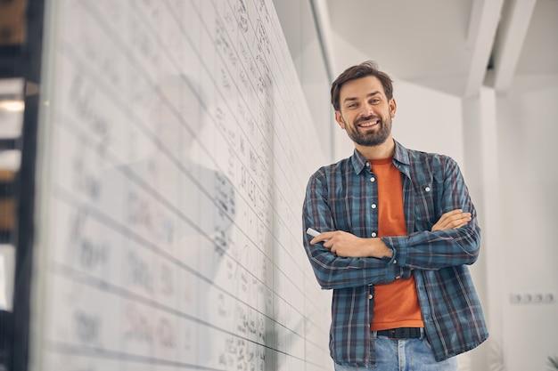 Beau travailleur masculin en chemise à carreaux regardant la caméra et souriant en se tenant debout près du tableau blanc