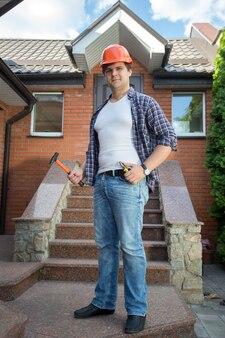 Beau travailleur souriant posant devant la maison avec escalier en pierre