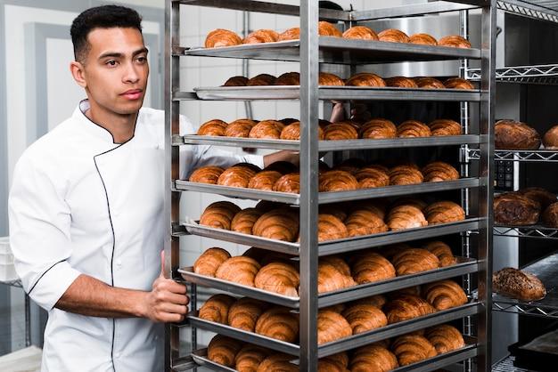 Beau travailleur en uniforme portant des étagères avec croissant à la boulangerie