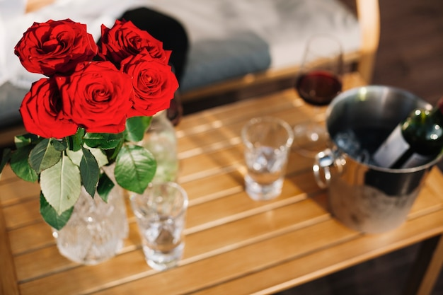 Beau vase de roses rouges sur table en bois