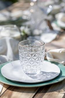 Beau vase en verre sur plaque en céramique sur une table pour le déjeuner