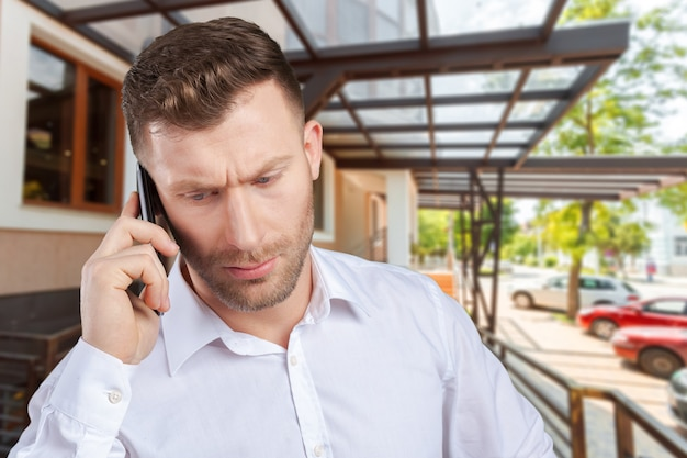 Beau vendeur parlant sur un téléphone mobile