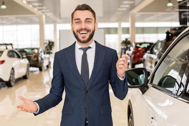Beau vendeur de voitures dans la salle d'exposition