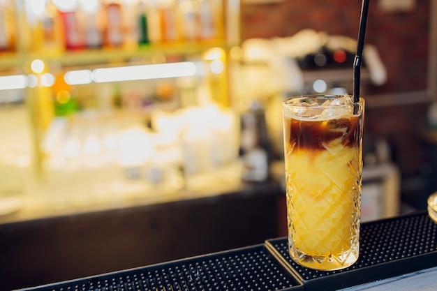 Beau verre à cocktail congelé avec de la glace, de la menthe et de l'ananas sur un comptoir de bar en bois foncé, fond clair bokeh.