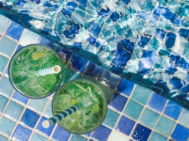 Beau verre avec un cocktail rafraîchissant sur le fond de la piscine